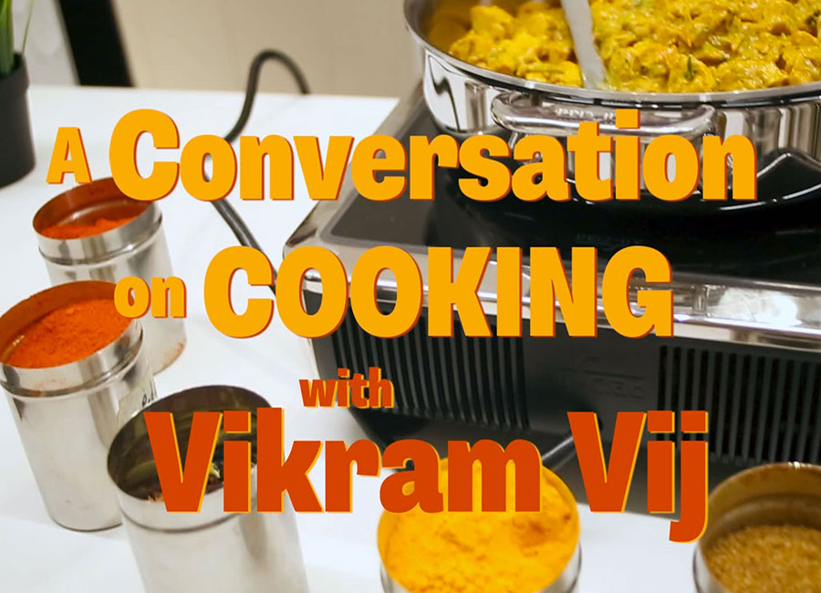 Text of the video Title A Conversation With Vikram Vij on Cooking appears over colourful spices and curry chicken cooking on a stove top