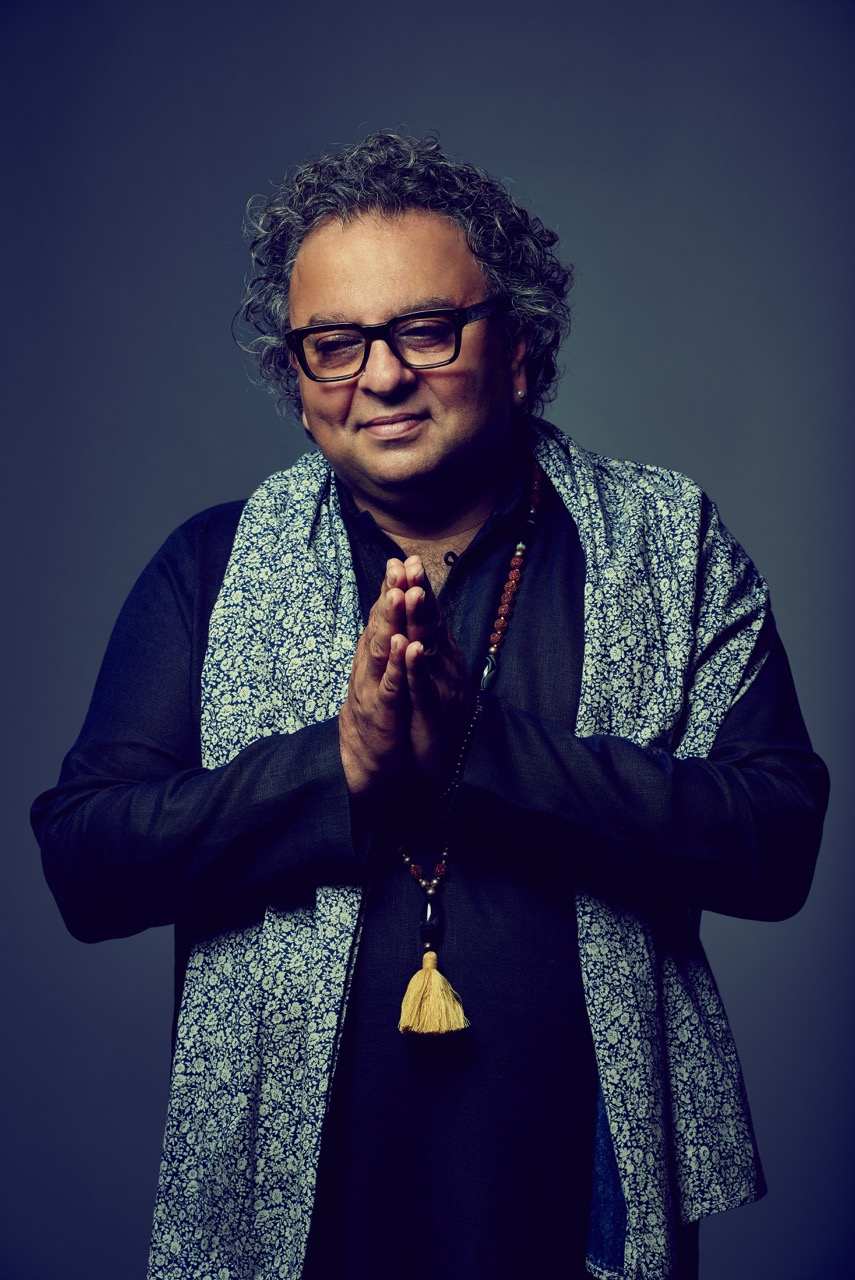 Chef Vikram Vij in prayer pose, wearing a large scarf, gold necklace