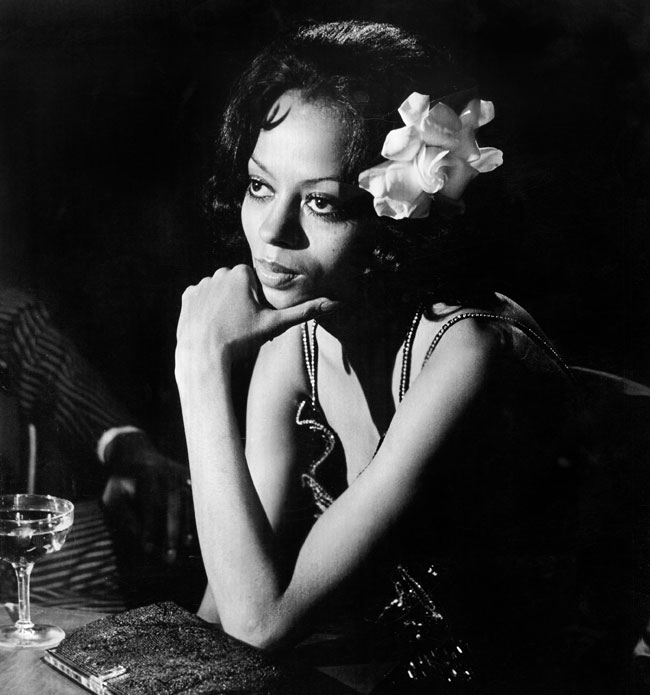 A black and white photo of Diana Ross, leaned forward resting an elbow on the table and her hand on her chin.