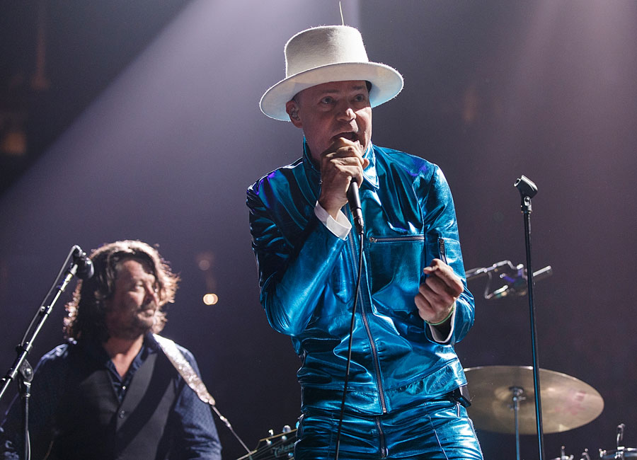 Gord Downie of The Tragically Hip performs onstage wearing a metallic blue suit and white hat during their 'Man Machine Poem Tour' at Rogers Arena.