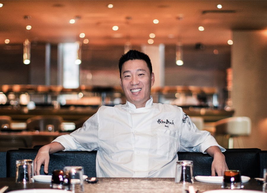 Chef Akira Back leaning back on a dining stool at his Toronto restaurant