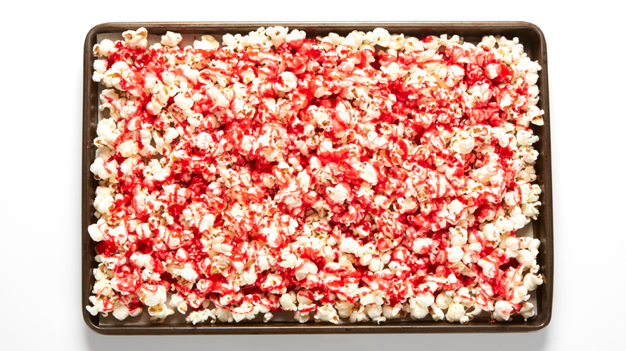 A pan of white popcorn with streaks of red on top.