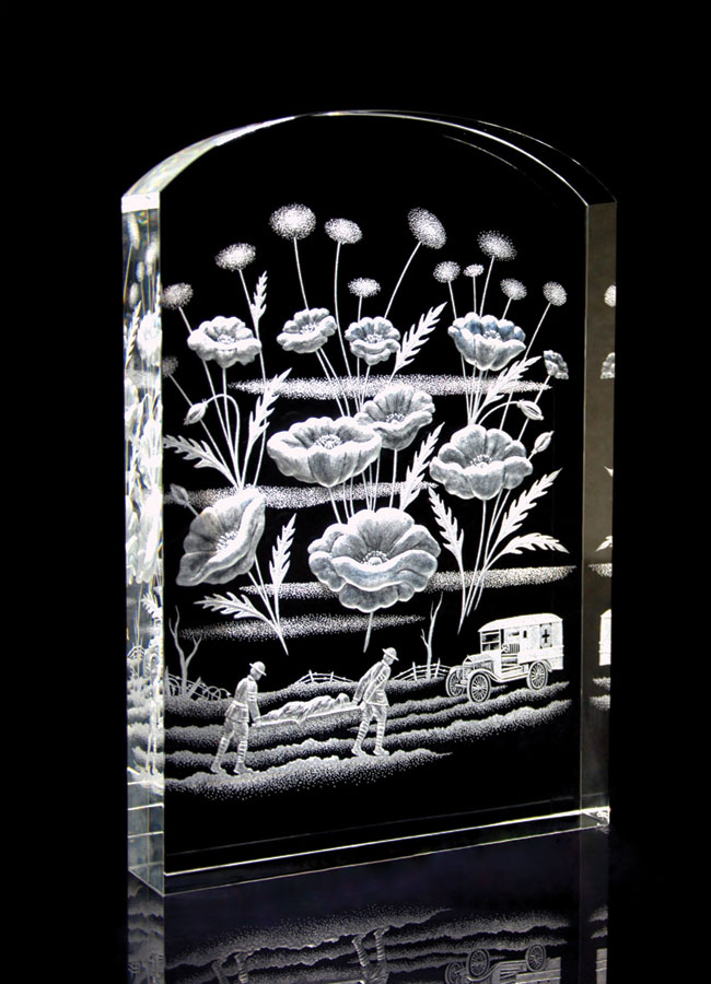 A crystal sculpture of a tombstone with flowers and two soldier carrying an injured comrade on a stretcher.