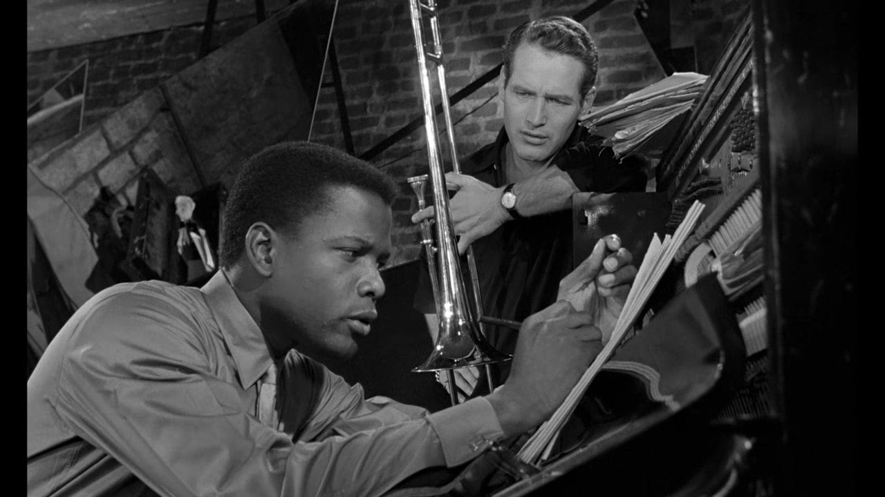 Sidney Poitier writing on a notepad at a music stand while Paul Newman, holding a trumpet, looks on.