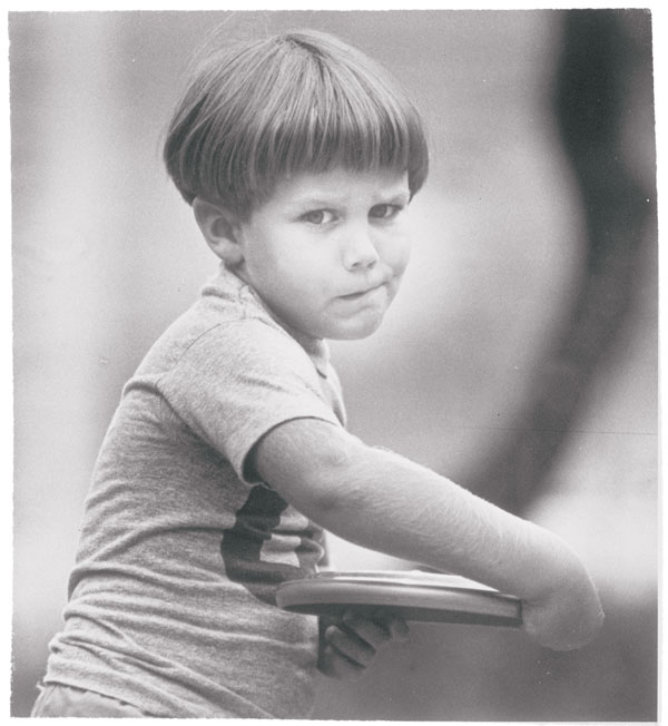A black and whit photo of a young boy with a bowl cut throwing a frisbee.