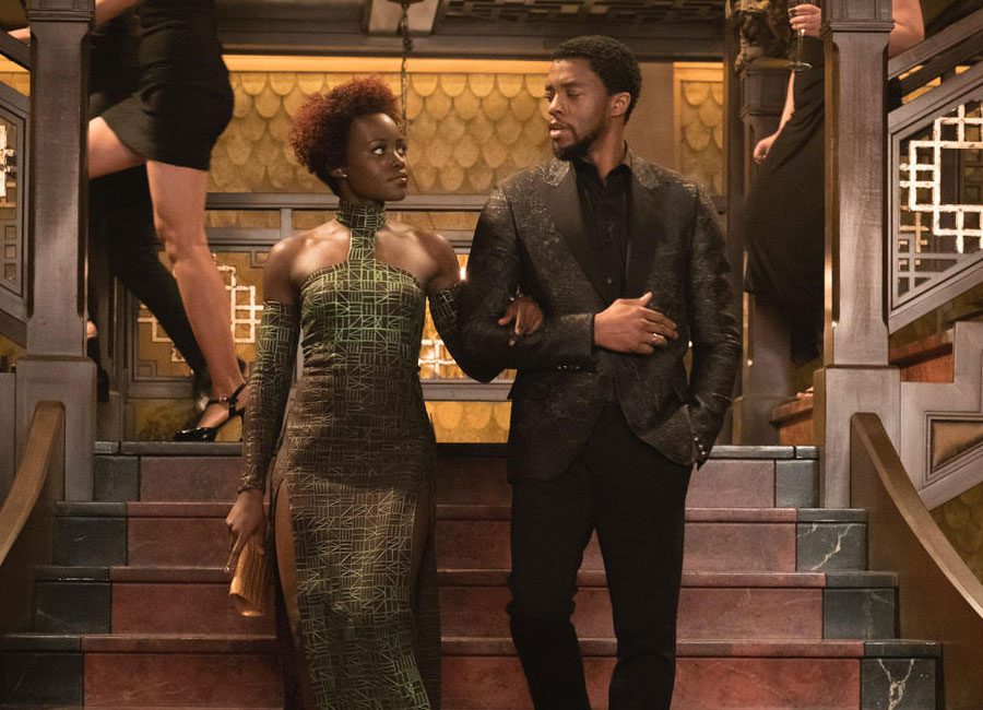 Lupita Nyong'o and Chadwick Boseman descend a staircase with arms linked.
