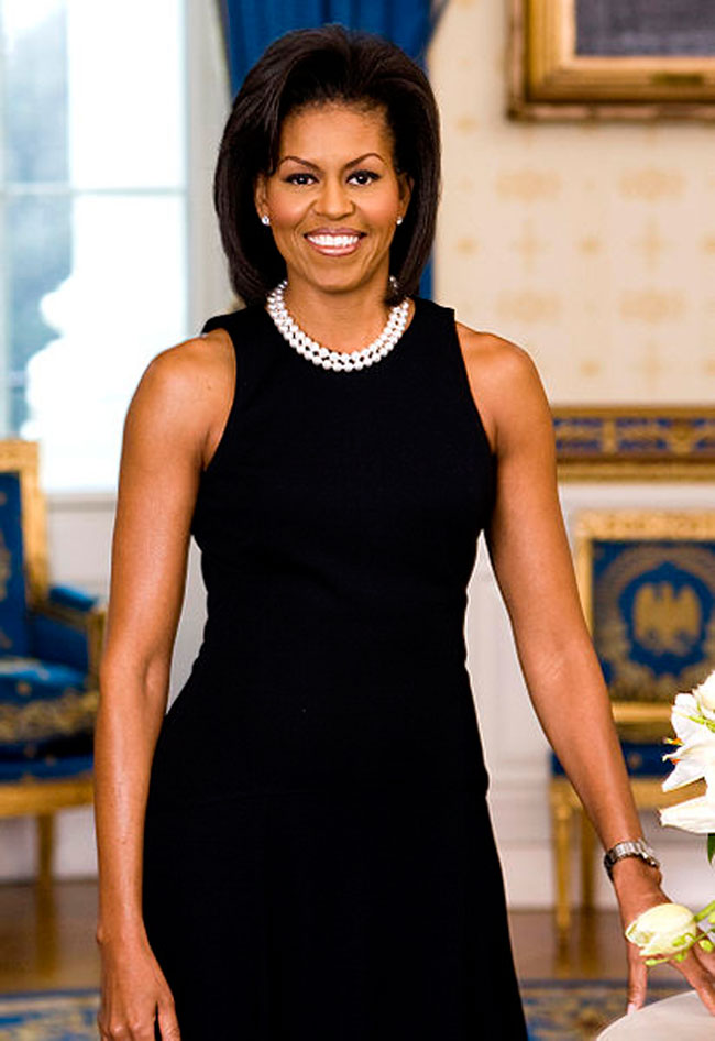 Michelle Obama wearing a sleeveless black dress and white pearls.