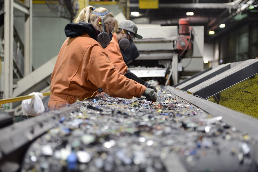 I worker wearing protective eyewear and a breathing apparatus sort through a pile of electronic parts at a recycling plant.