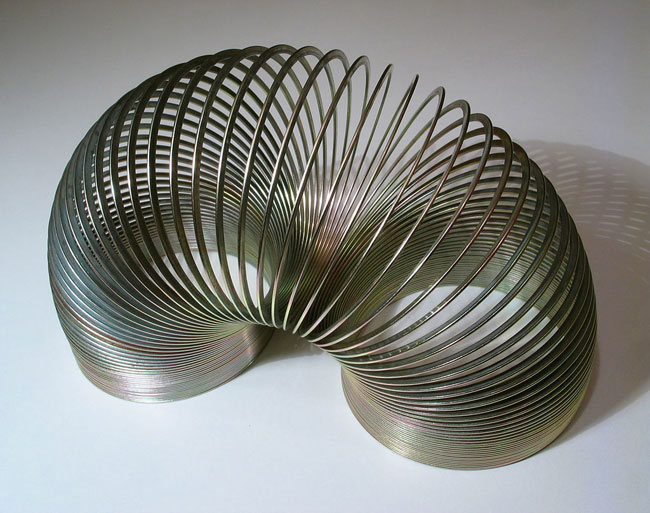 A steel slinky standing on both ends.