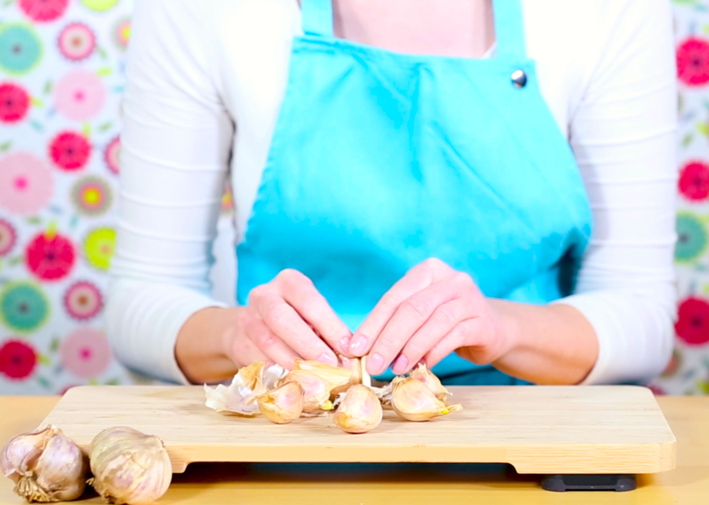 Colourful image with a woman in a sky blue apron who is separating garlic cloves from the large bulb