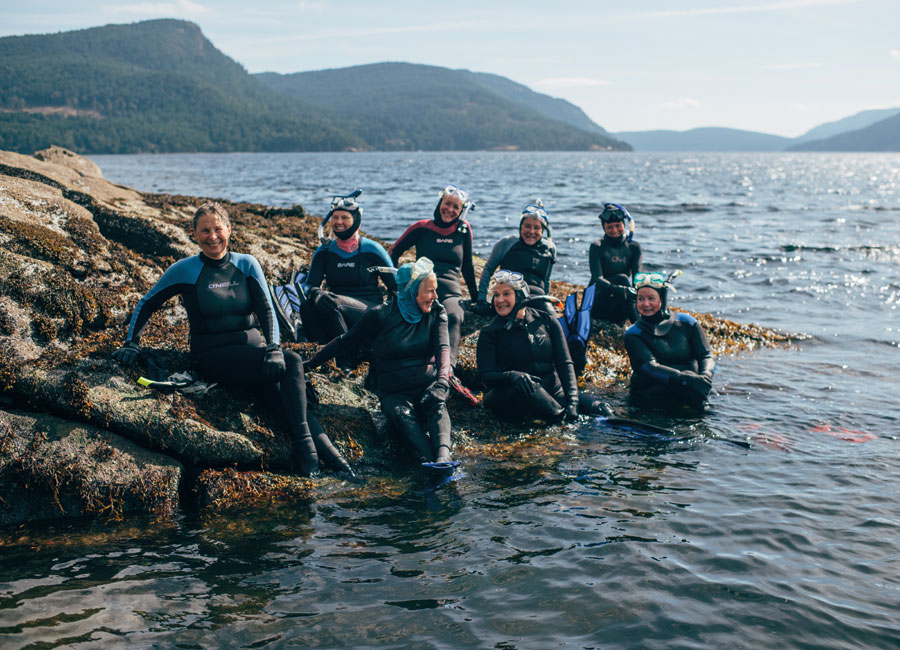 The Seals swimming club wearing their wet suits and socializing on the rocky shores of Salt Spring, British Columbia.