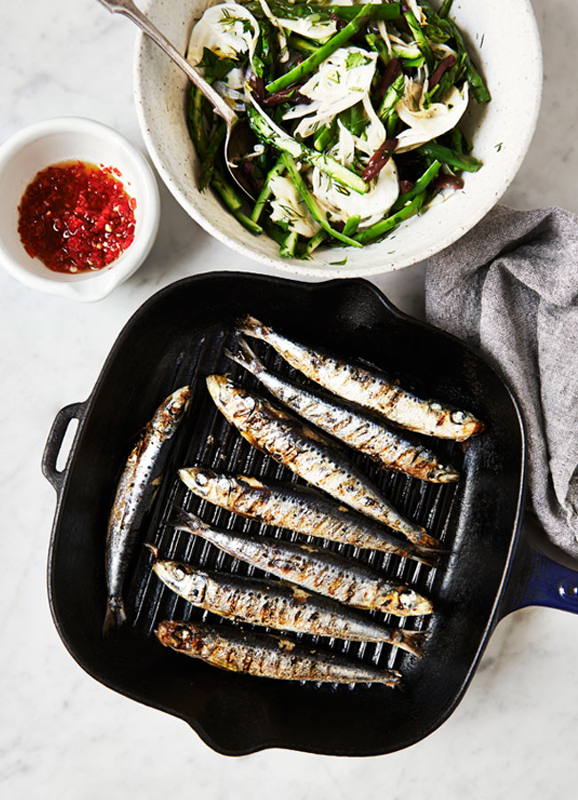 Sardines in a grill pan with a bowl of Fennel, Asparagus and Olive Salad