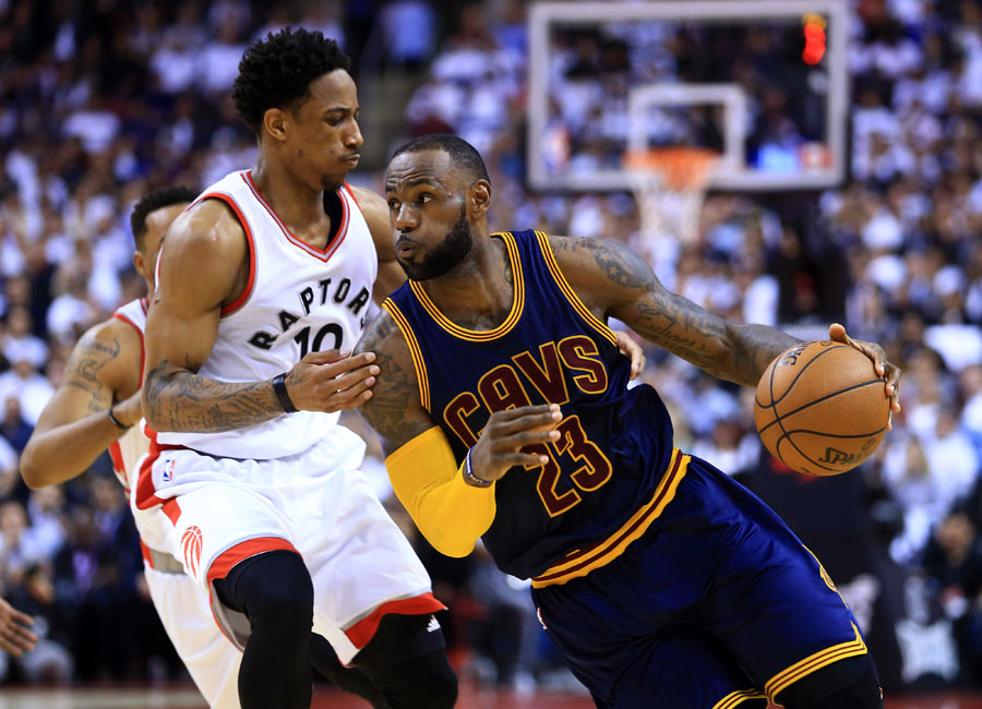 LeBron James drives to the basket as he put a shoulder into DeMar DeRozan.