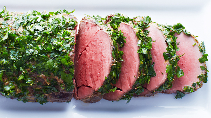 Medium rare horseradish-crusted beef tenderloin with four slices cut and displayed on a white plate.