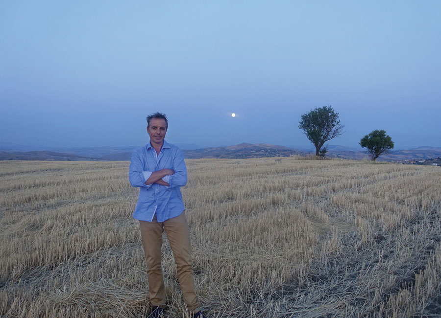 Author Dan Buettner standing in a field of dry straw at dusk.