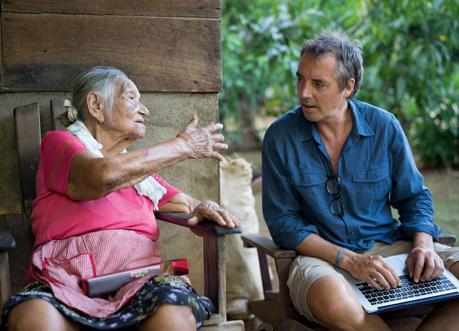 Dan Buettner converses with an older woman as he takes notes on his lap-top.