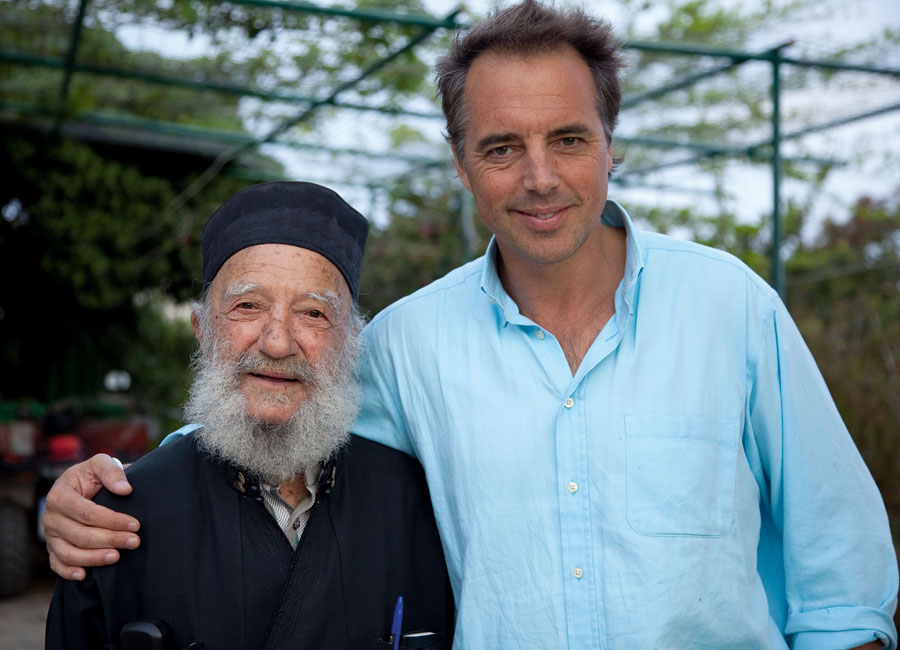 Dan Buettner poses with an older bearded man. Both men are smiling.