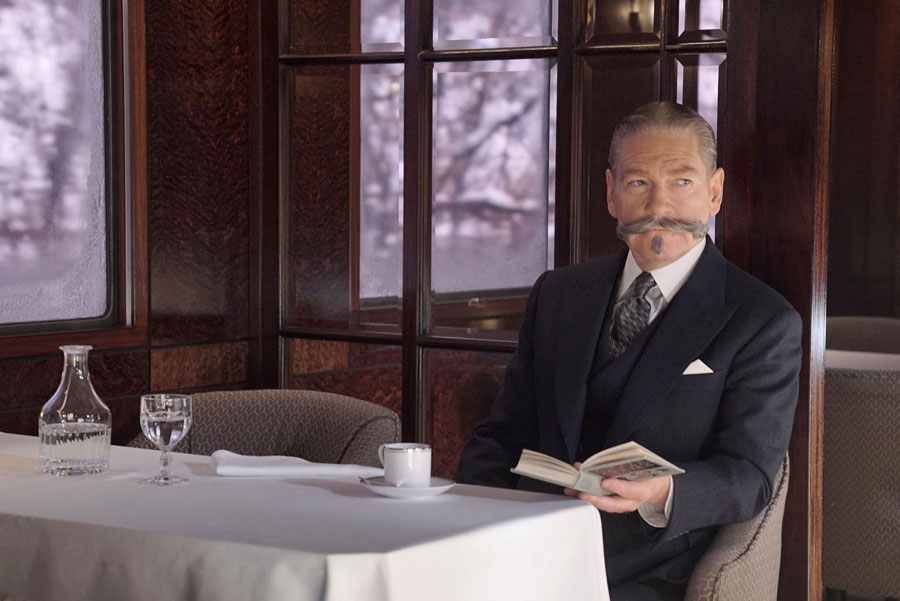 Kenneth Branagh as Hercule Poirot in Murder On The Orient Express dressed in a dark suit holding a book open with one hand.