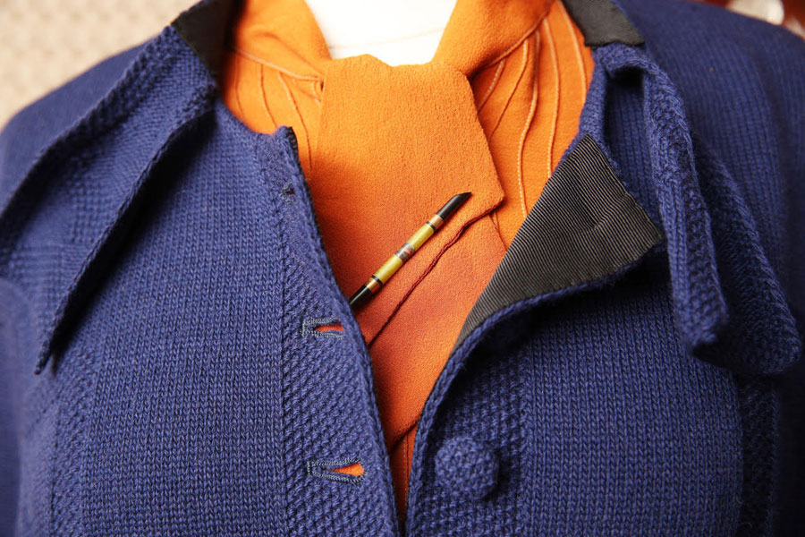 A violet wool jacket with the first two buttons undone displaying a subdued orange scarf.