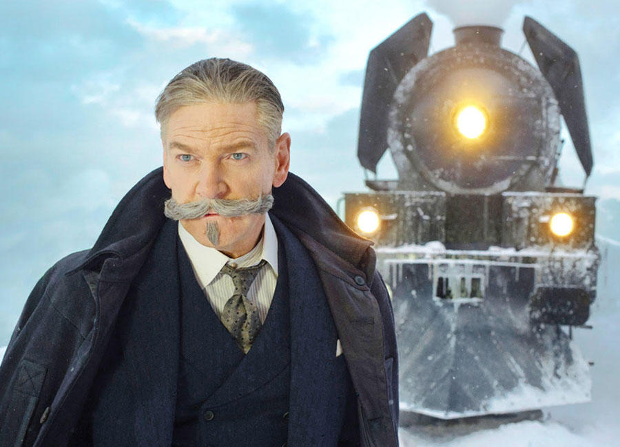 enneth Branagh as Hercule Poirot in Murder On The Orient Express posing in front of the train.