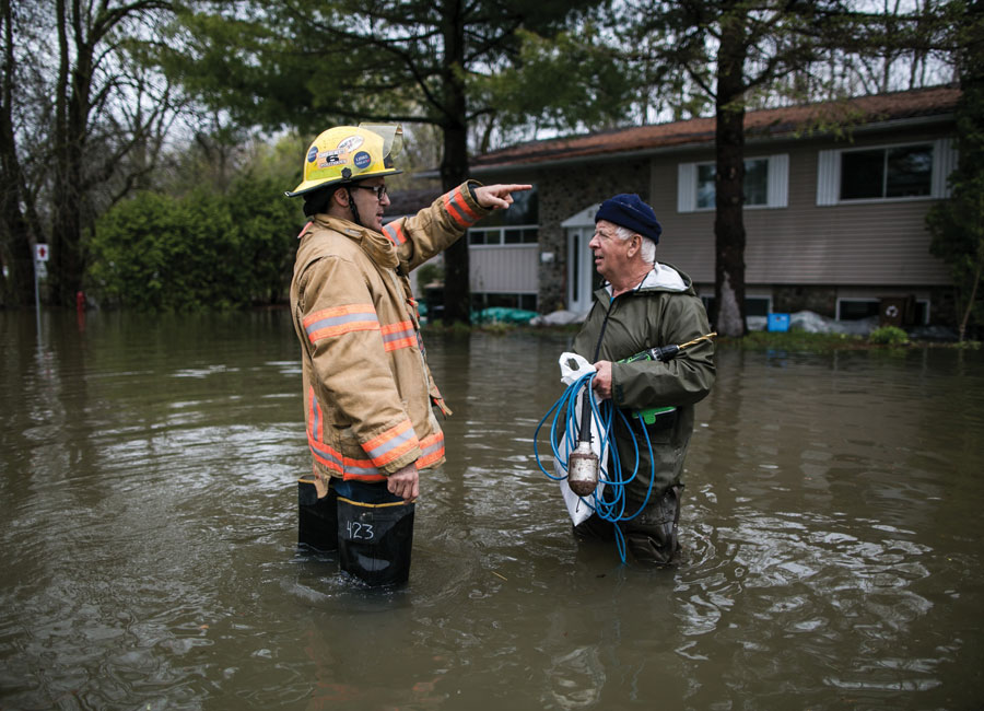 An older man speaking with an emergency relief worker in knee hight flood waters.