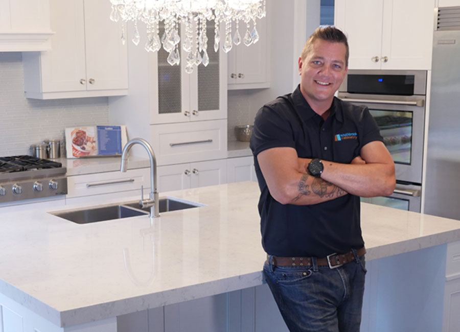 Contractor and TV personality Damon Bennett leans against the island of a kitchen featuring white cabinetry and stainless appliances.