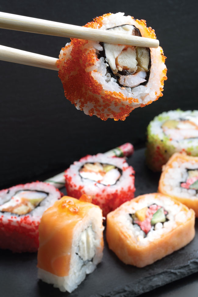 A pair of chopsticks holding a sushi roll over a plate of an assortment of sushi.