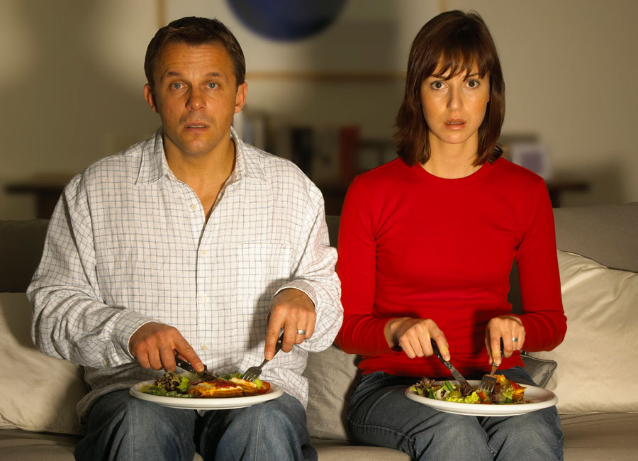 Two people staring blankly at a television screen while they cut into their dinner.