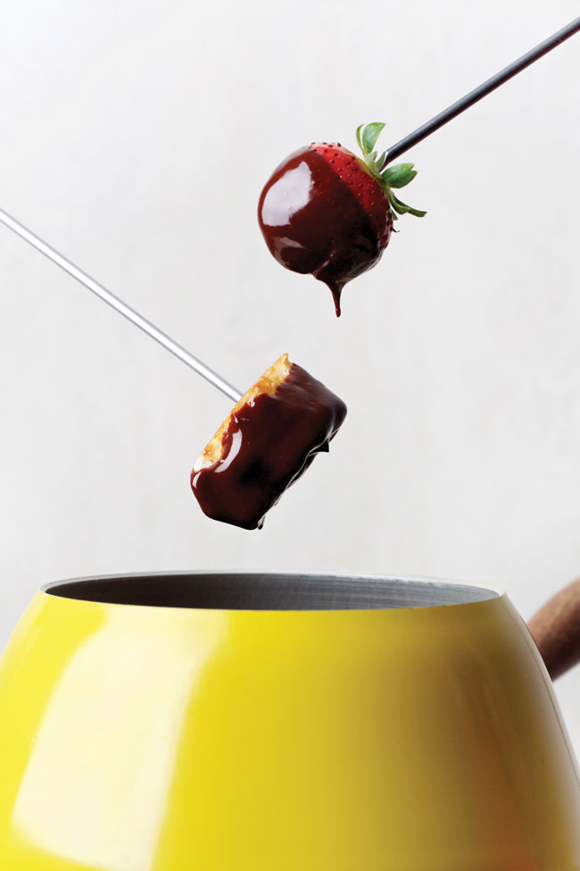 A skewer holding a strawberry dripping in chocolate emerging from a fondue pot.