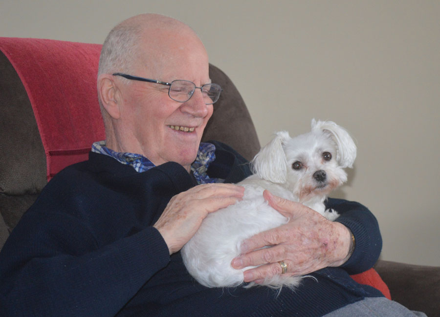 Oliver, a senior sits with his small white dog named Saffi