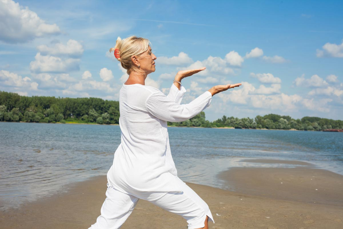 Woman doing tai chi o the beach