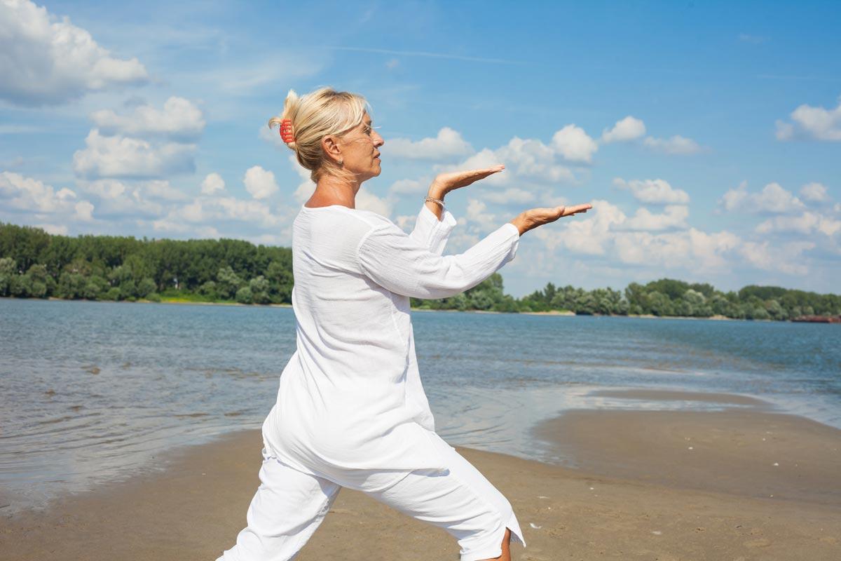 Woman doing tai chi o the beach