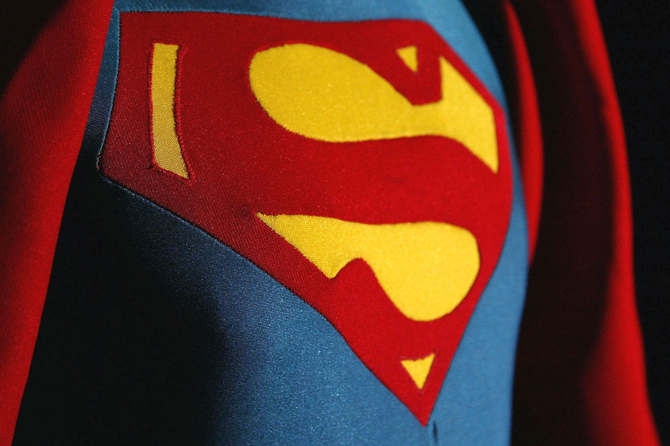 A closeup of the superman emblem on the chest of superman.