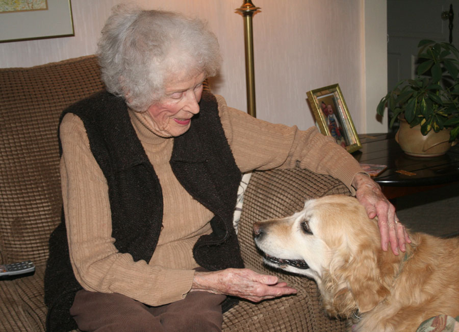 A senior woman sits on a sofa and pets her golden retriever seated at her feet