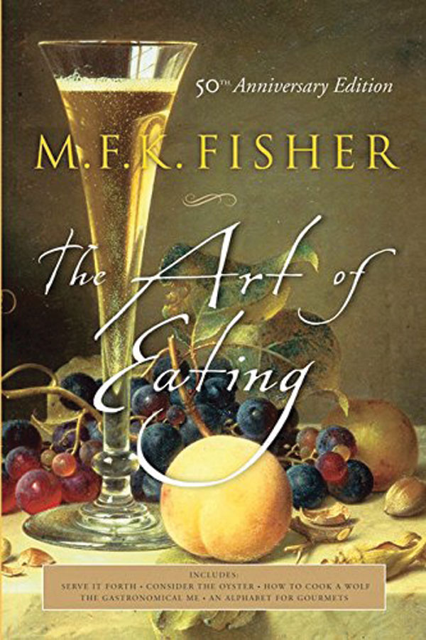 The book cover for The Art of Eating. A photo of a bunch of grapes and a peach beside a glass of wine is overlaid with the title of the book written in cursive.