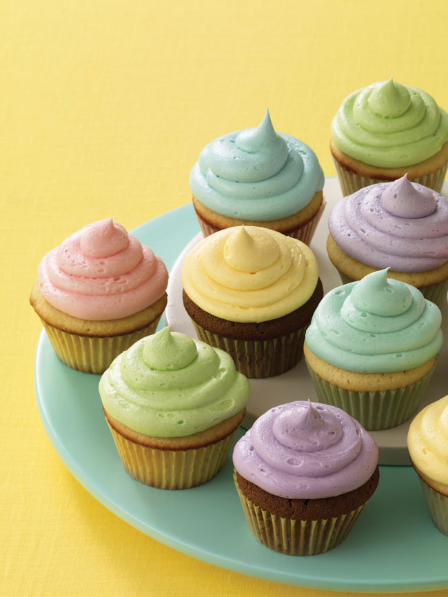 Multicoloured cupcakes sitting on a green plate.