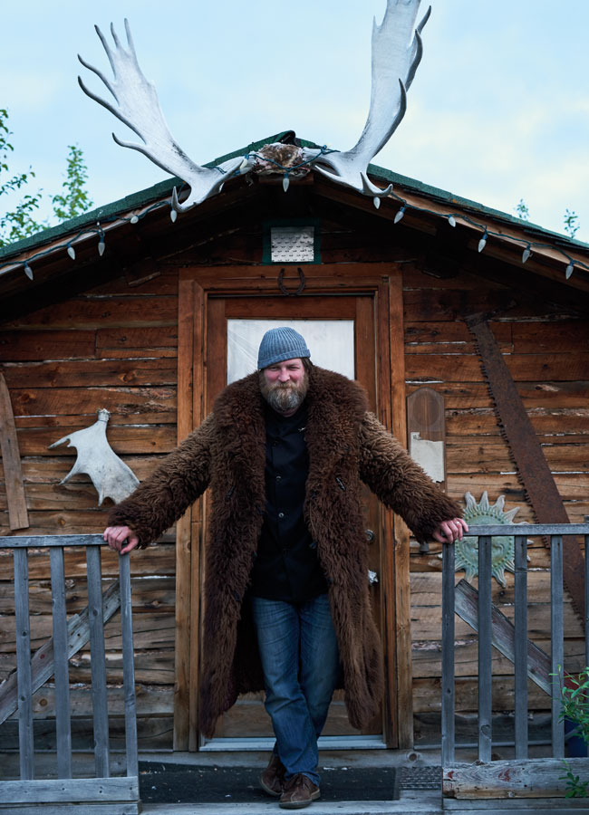 A bearded man wearing a grey toque and dark brown fur jacket posing in front of the entrance of a cabin with moose antlers fixed to the roof.
