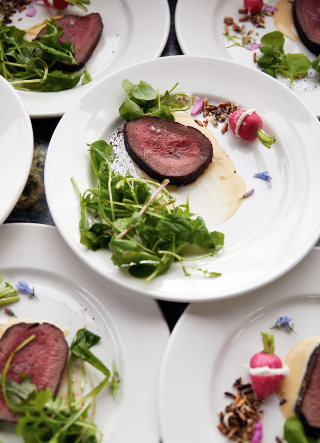 Roasted Elk Rack on a white plate with greens.