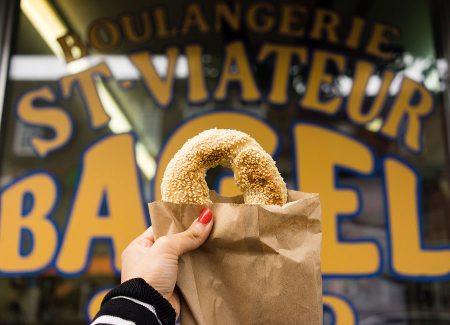 A bagel is held up in front of the store front of St-Viateur bagel shop in Montreal.