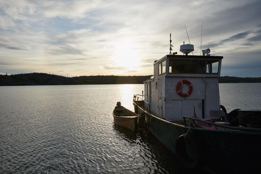 A boat leaving ST. John's Harbour travelling toward the sun on the horizon.