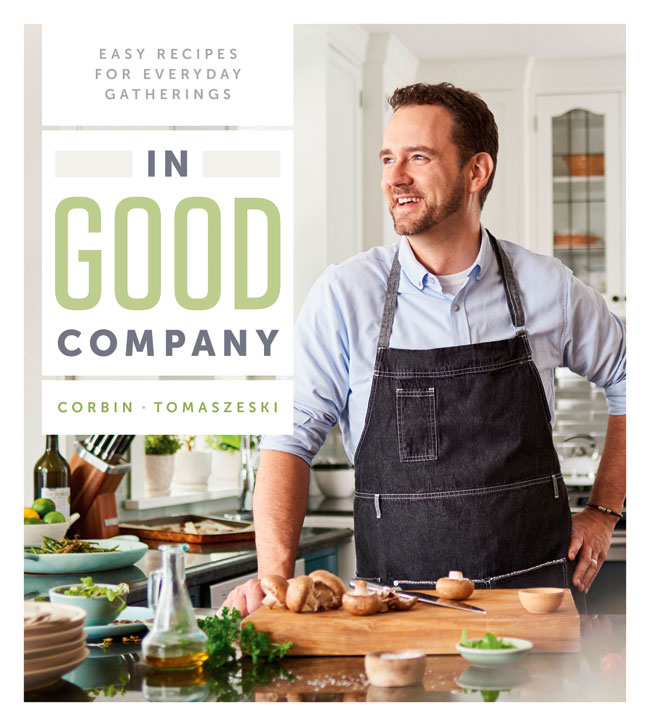 Book cover for In Good Company. Corbin Tomaszeski standing at a kitchen counter and cutting board with freshly chopped mushrooms laying on it.