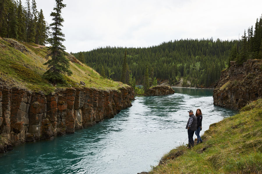 Two people stand at at the edge of turquoise water surrounded by lush grass and pine trees.