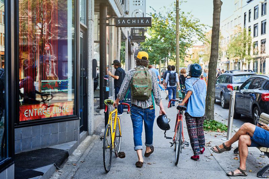 Two locals walk their bike along the sidewalk passing coffee shops in the Mile End neighbourhood in Montreal.