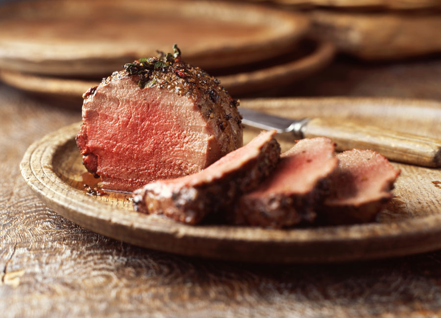 A small roast beef with several slices cut out of it on a wooden plate.