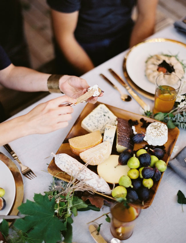 An assortment of cheese on a cheeseboard with a pair of hands spreading a soft cheese on a cracker.