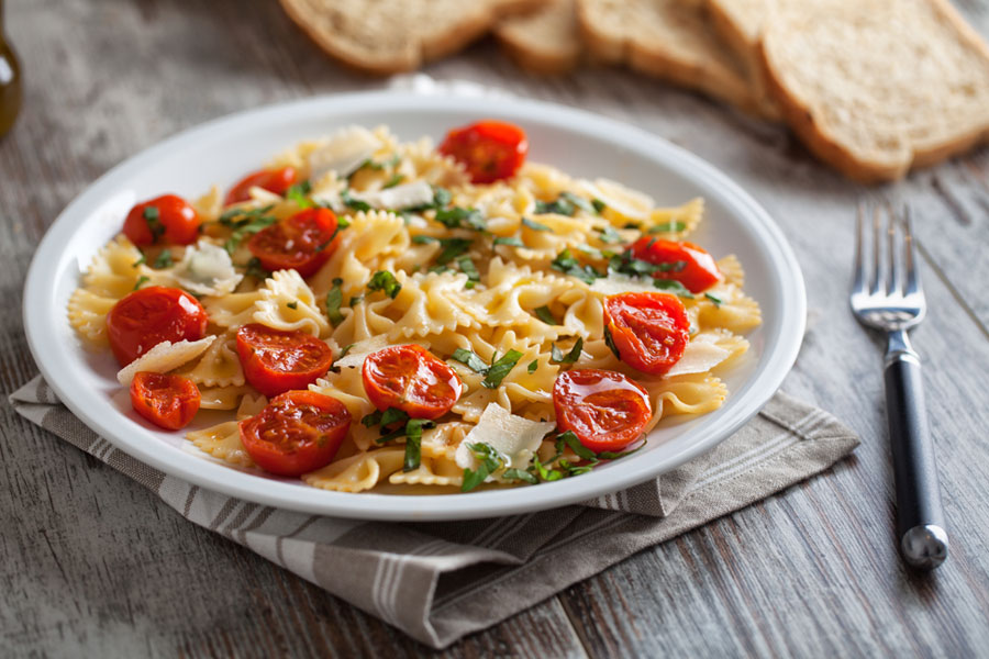 A bowl of bow tie pasta with sun dried tomatoes on a wooden table with a fork and bread displayed next to it.