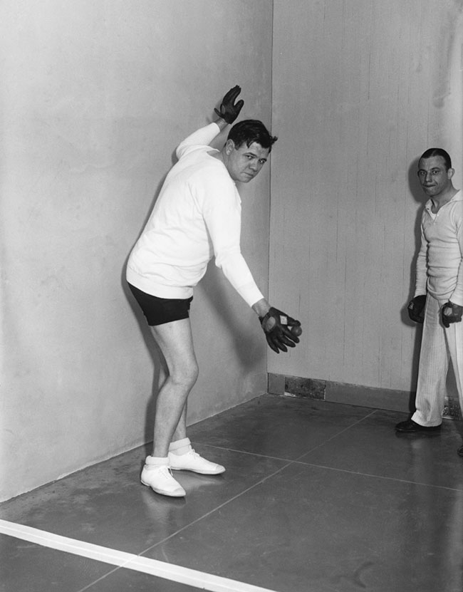 Babe Ruth holds the ball up to serve at a handball court.
