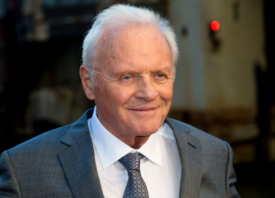Anthony Hopkins wearing a grey suit and smiling.