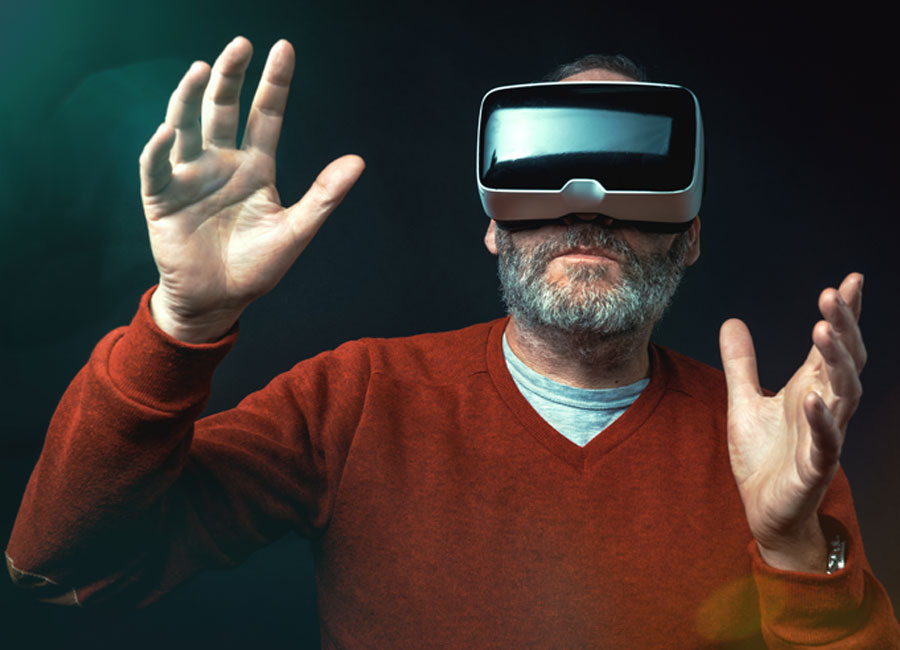 A man with a grey beard dons virtual reality glasses and holds his hands out in front of him.