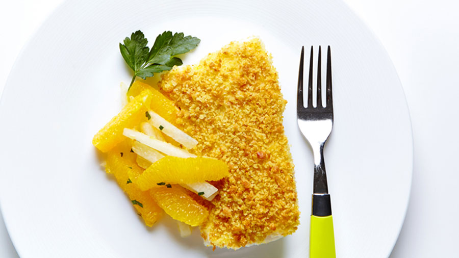 Baked Lemon Cod with Orange Jicama Salad beside a fork with a neon yellow handle on top of a white plate.